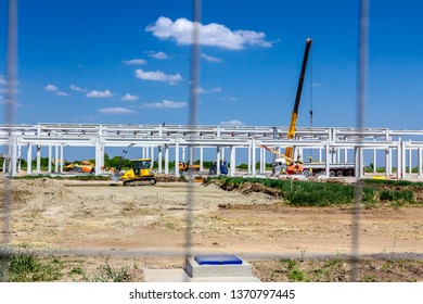 View on building site trough metal fence, unfinished concrete edifice, construction zone, people are working.