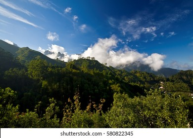 View on central mountains of Madeira. Green mountains with white clouds and blue sky. Madeira island, Portugal.