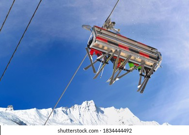 view on chairlifts with skiers from below on blue sky and peak mountain snowy