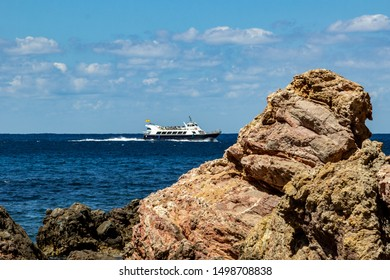 View on the coast at bay Cala Tuent on balearic island Mallorca, Spain on a sunny day with clear blue water, rocky coastline and ferry ship