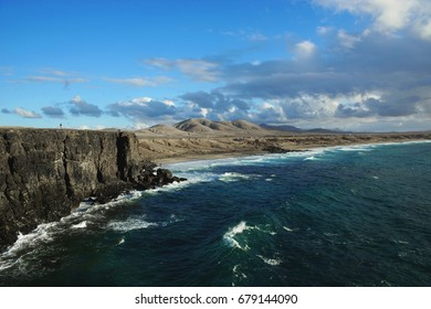 View on a coastline with huge rocks and sandy beach on a sunny evening with soft light. Mountains at horizon and clouds at the sky