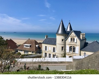 View on coastline and town Arromanches in Normandy France with remnants of piers in the sea where allies in world war disembarked, on a sunny summer day