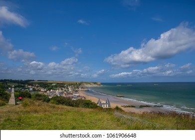 View on coastline and war memorial near town Arromanches in Normandy France with remnants of piers in the sea where allies in world war disembarked, on a sunny summer day