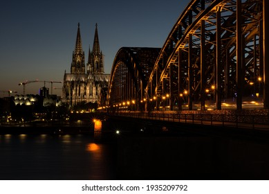 View on cologne cathedral and a arch bridge across the river rhine, at night. Bridge and cathedral are illuminated in a warm light.