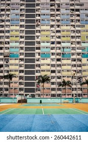 View on colorful apartment buildings and court with palms in Hong Kong