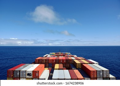 View on the containers loaded on deck of the large cargo ship. She is sailing through calm, blue ocean.
