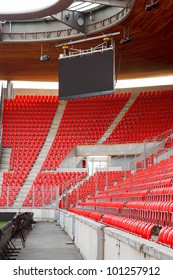 View on corner of an empty football (soccer) stadium with red seats and projection screen.
