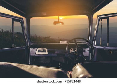 View on the dashboard of the car. Sunset and mountains is in front of the car.