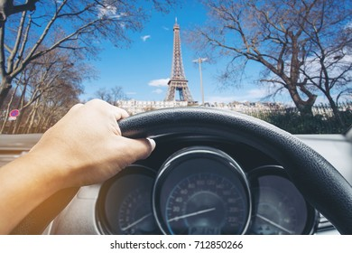 View on the dashboard of the truck driving.The driver is holding the steering wheel. Eiffel tower is in front of the car.