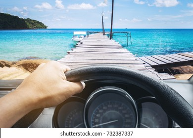 View on the dashboard of the truck driving.The driver is holding the steering wheel. Sea and wood bridge is in front of the car.