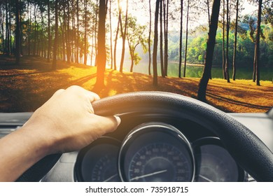 View on the dashboard of the truck driving.The driver is holding the steering wheel. Green forest is in front of the car at Pang Ung in Mae Hong Son ,Thailand.