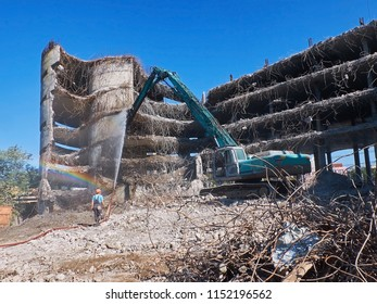 View on deconstruction works by heavy pneumatic crane excavator with special equipment and worker with water hose to avoid dust. Buildings and houses Industrial destroyer