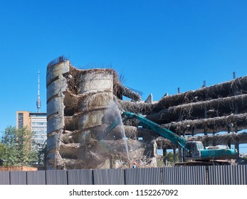 View on deconstruction works by heavy pneumatic crane excavator with special equipment. Buildings and houses Industrial destroyer. Illegal buildings