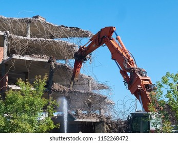 View on deconstruction works by heavy pneumatic crane excavator with special equipment. Buildings and houses Industrial destroyer