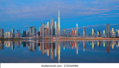 View on Dubai skyline with reflection in the river at sunrise, Dubai, United Arab Emirates