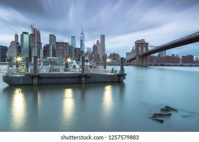 View on east river ferry and Downtown manhattan at sunrise with long exposure