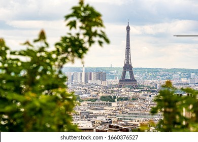 View on Eiffel Tower from Montmartre viewpoint in Summer whith trees and sunny clouds