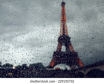 View on the Eiffel Tower through the window with rain drops. France. Paris. Dark dramatic colors