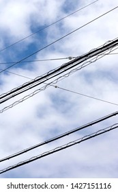 View on electricity cables high up in the sky in a city environment. The cables are used for transporting energy and current. The cables are visible against a beautiful blue sky and white clouds
