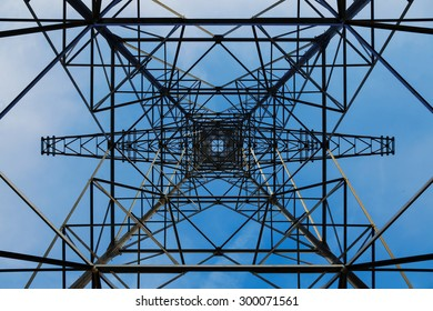 A view on electricity pylons from below against the sky.