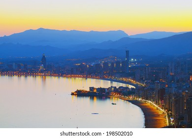 View on evening city with a sea beach on a background of mountains in the mist (Spain, Benidorm)