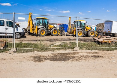 View on few excavators through a fence wire, parked at construction site.