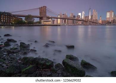 View on finance district and Brooklyn bridge in Manhattan from east river at sunrise.