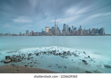 View on finance district in Manhattan from Hudson river with rocks on the foreground,Long exposure shot