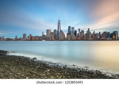 View on Financial District from Hudson river beach at sunset with long exposure