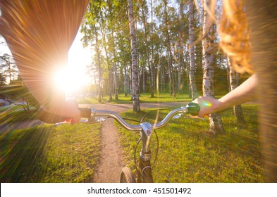 view on girl hands, who ride by bicycle in sunset time in the park. Halth evening concept.