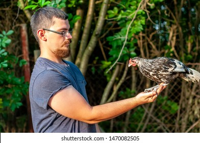 View on a handsome bearded man holding and training a Hamburg Chicken in his hands on a sunny day.