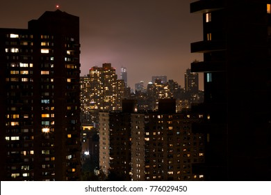 View on Harlems skyscraper at night, big silhouettes and its a bit foggy between the buildings. The city-light is glowing in  the haze.