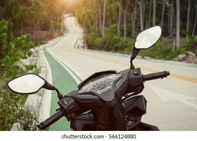 View on the highway from scooter. Mirrors and speedometer over the sunset in the tropical forest.