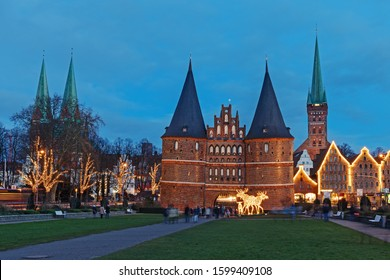 View on the historic city center of Luebeck (Lübeck) with the famous Holstentor and the towers of two churches, Marienkirche (left) and Petrikirche at Christmas