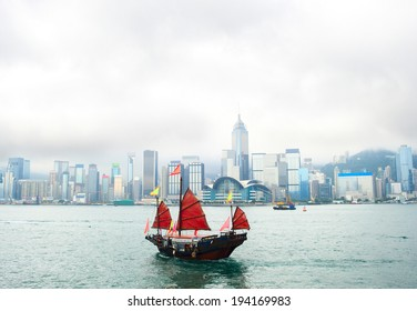 View on Hong Kong downtown from the sea with traditional chinese sailboat