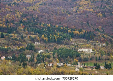 View on the houses located on the hill-side with forest foliage of the mountains in Trentino, Italy, Europe