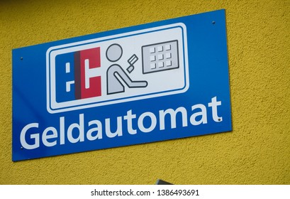 """View on isolated blue sign on yellow wall indicating ATM (German letters """"Geldautomat"""" meaning automatic teller machine)"""