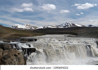 View on isolated river flowing through wide black barren plain forming waterfall. Partly snow capped mountains in the horizon. Iceland.