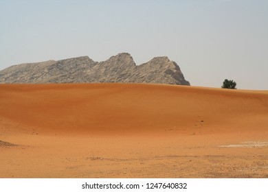 view on isolated rock over red sand dunes in Oman desert