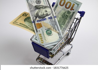 View on isolated shopping cart modell with us dollar paper bills, white blank background - gross national domestic product concept