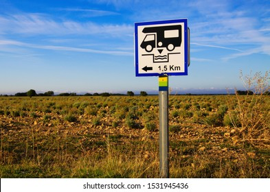 View on isolated white direction sign with camper against blue sky and lavender field. Sign gives information for next cesspool for feces disposal. Provence, France