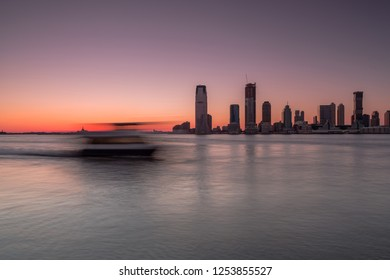 View on Jersey city with passing by ferry at sunset,Long exposure