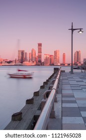 View on jersey city from the pier with floating boat during sunrise