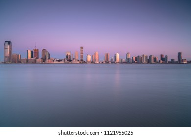 View on Jersey city from water during sunrise from