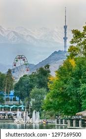View on the Kok Tobe tower in Almaty, lake and ferris wheel in Gorky Park, Kazakhstan