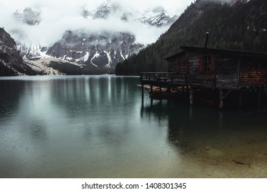 View on the Lago di Braies up high in the italian dolomites with a boats house in the right corner, a green blue lake in the center an in cloud and snow covered majestic mountain in the background