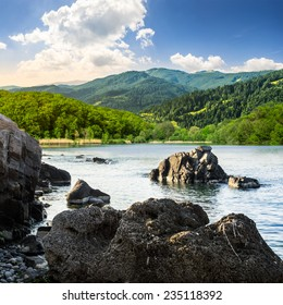 view on lake with rocky shore and some boulders near forest on mountain  with high vista far away