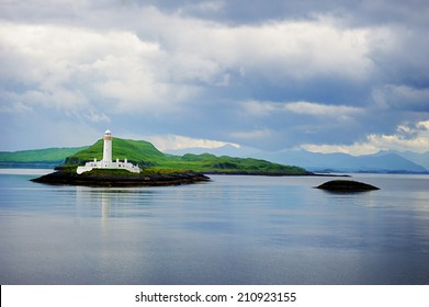 View on lighthouse in the cloudy morning with reflection in the water: Scotland, Oban