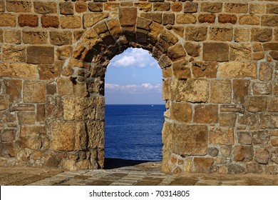 View on a lonely white sail in the dark blue sea through a window in an old fortification
