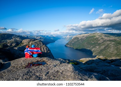 View on Lysefjord fjord from the Preikestolen pathway. Couple of tourists with the flag of Norway visiting the natural attractions.